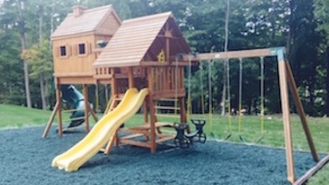 Wooden Tree House Jungle Gym on Green Rubber Swing Set Mulch with Borders